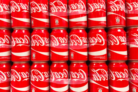 A large group of Coca-Cola red cans stacked in a supermarket